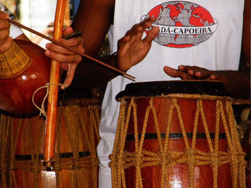 An atabaque and berimba being played side by side