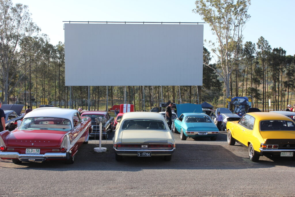 Several classic cars gather at a drive-in movie theater to watch a movie at the San Jose drive-in movie theater
