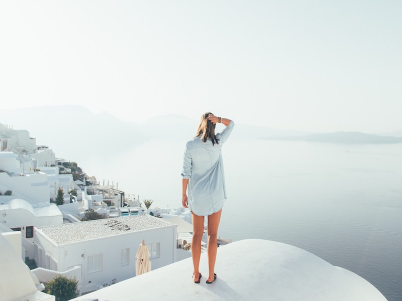A woman in lightweight clothing overlooking santorini
