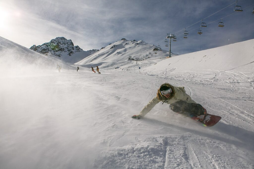 An accelerating snowboarder boards down a mountain under a perfect blue sky.
