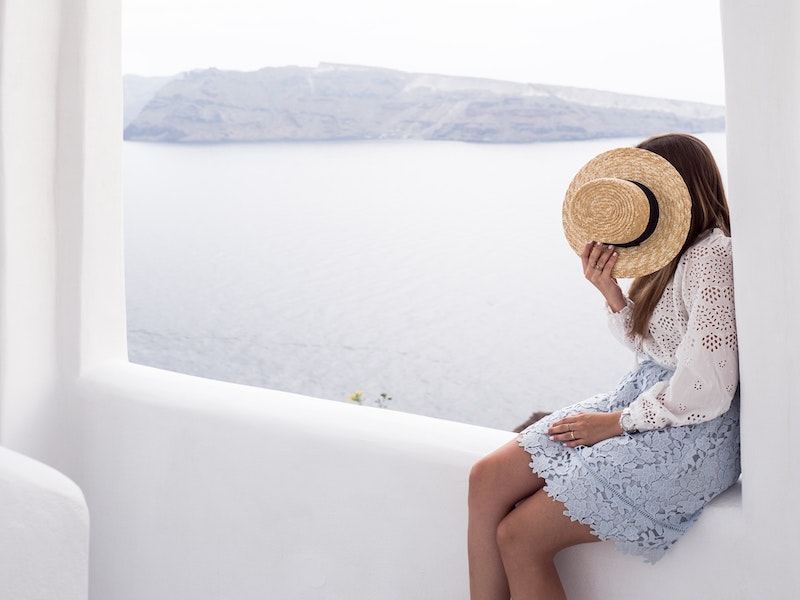 A women dressed in white in Oia Santorini with a sun hat