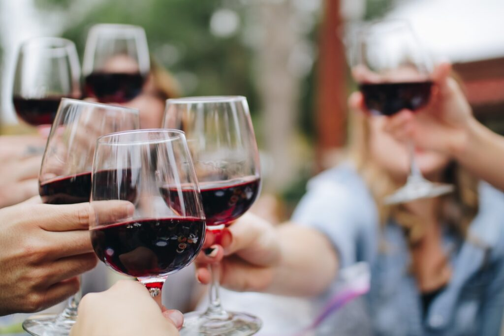 A group of friends clinking full glasses of red wine at the Wine Merchant and Bar located in San Jose, California