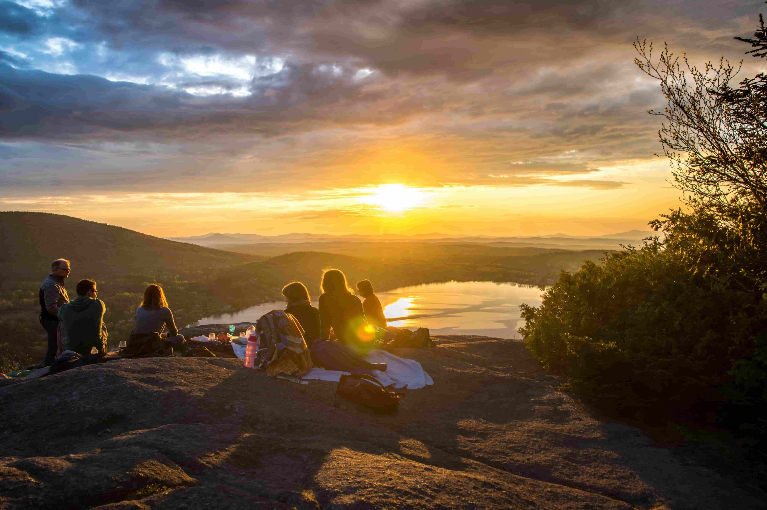 Group of travellers having sunset picnic