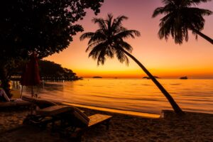 Sunset and sun loungers on beach in Thailand - where to stay in Koh Lanta