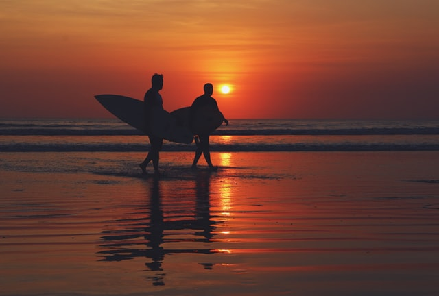 Two men surfing at sunset