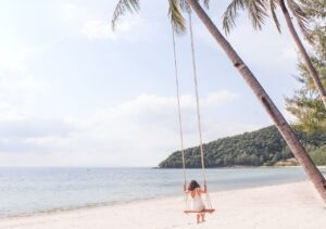 Woman on swing on Island in Thailand